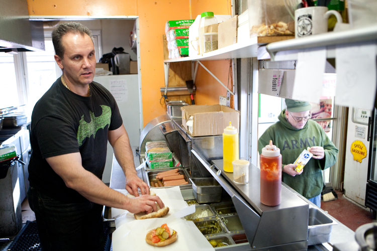 "John Cappas, owner of Johnny's Wee Nee Wagon, prepares hotdogs for a customer at the restaurant in Markham, Ill. on Wednesday, November 14, 2012.  Cappas, a former cocaine dealer, was released from serving 15 years in prison in 2004 and has since released a book titled ""Tall Money,"" the story behind his life."