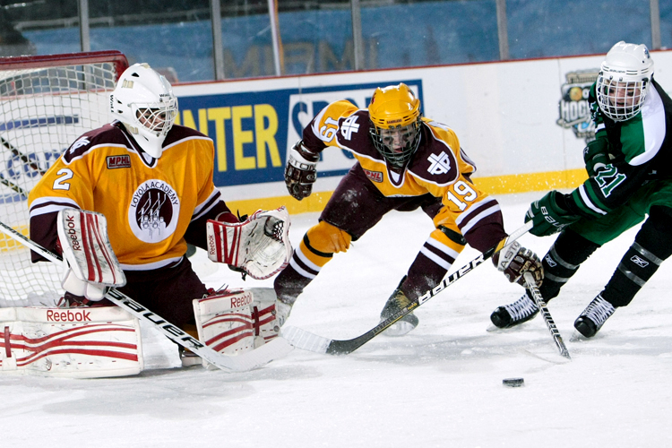 Loyola's Joey Schaefer (19) tries to clear a puck away from the front of the net while New Trier's Jesse Arnold (21) attempts a shot on goal in the second period during the Hockey City Classic game at Soldier Field on Saturday, February 9, 2013. New Trier defeated Loyola 3-1. | Michael Jarecki ~ For Sun-Times Media