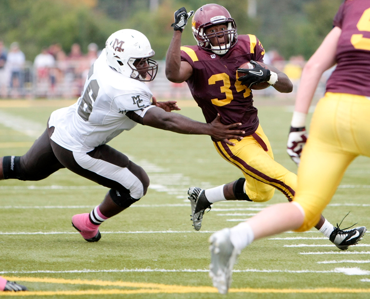 Loyola senior Julius Holley (34) tries to get outside of Mount Carmel senior Enoch Smith Jr. (56) during the home game against Mount Carmel on Saturday, October 5, 2013.  | Michael Jarecki/For Sun-Times Media