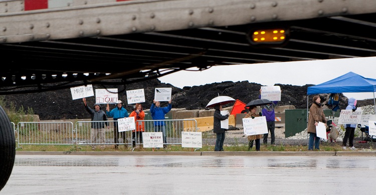 FAiR Coalition members battle the rain while protesting the opening of a new runway at Chicago's O'Hare International airport at the intersection of Irving Park Road and Taft Avenue near the airport on Thursday, October 17, 2013.  | Michael Jarecki/For Sun-Times Media