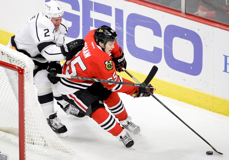 Chicago Blackhawks forward Andrew Shaw (65) carries the puck around the net while being pressured by LA Kings defenseman Matt Greene (2) in the second period during the home game on Sunday, December 15, 2013.  | Michael Jarecki/For Sun-Times Media