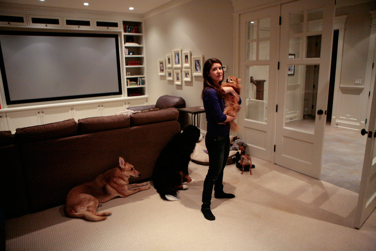 "Julie Greco holds her pomeranian ""Sugar"" while the other rescue dogs lounge in the entertainment area of the 6,600 square foot home on Thursday, January 30, 2014.  