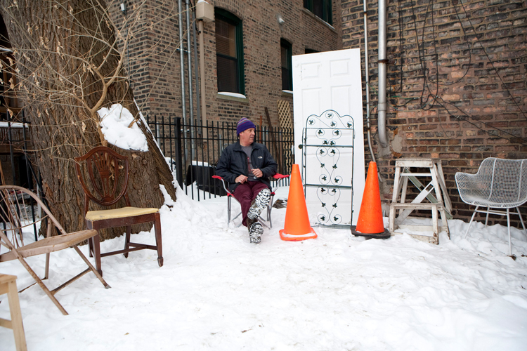 "Artist Curtis Locke sits in chair that is part of his collection of ""dibs"" parking space savers in his backyard on Saturday, February, 15, 2014.  Since early February this year Locke has been collecting people's ""dibs"" parking space savers throughout Chicago neighborhoods.  He plans to make a public art installations with the collected pieces before the winter is over.   
