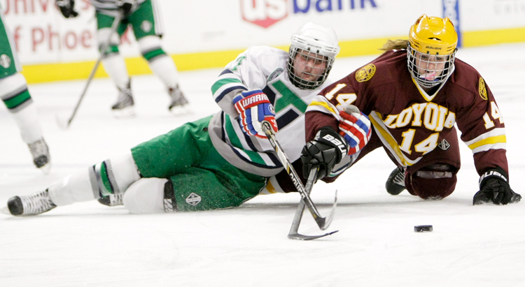 New Trier junior Rebecca Lindblad (7) battles Loyola freshman Valerie Caldwell (14) for the puck early in the Illinois State Championship game at the United Center in Chicago on Thursday, March 20, 2014.  New Trier defeated Loyola 3-2 in double overtime.    | Michael Jarecki/For Sun-Times Media