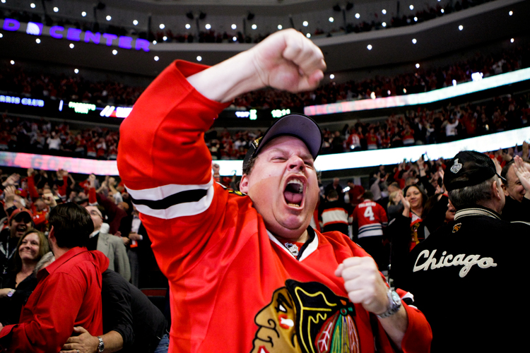 Chicago Blackhawks season ticket holder Ron Kelly of Hawthorn Woods, Ill. cheers after forward Marcus Kruger (16) scored an empty net goal late in the third period to beat the Blues 2-0 in Game 3 of the first-round NHL hockey playoff series at the United Center in Chicago on Monday, April 21, 2014. | Michael Jarecki/For Sun-Times Media