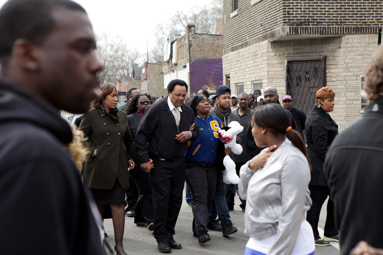 Tymeka Woods (3rd from left) is lead up to the memorial site for her son, 16 year old Michael Flournoy III before the start of a vigil where Flournoy was shot and killed near the corner of 93rd street and Dobson Ave. on Chicago's south on Sunday, April 6, 2014.  Flournoy was shot and killed near that intersection on Saturday, April 5, 2014.   | Michael Jarecki/For Sun-Times Media